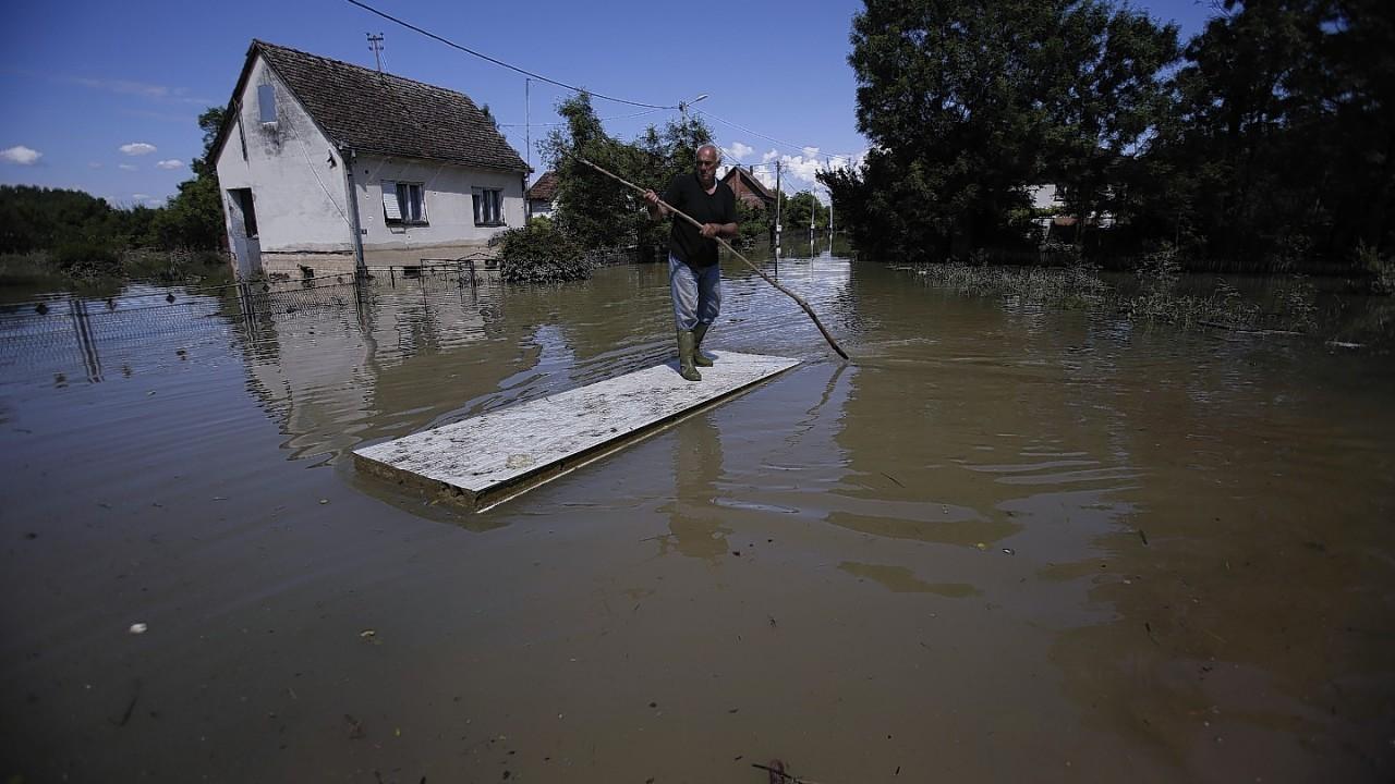Bosnian man Lazar Vakic  paddles through floodwater  near the Bosnian town of Bosanski Samac along river Sava, 200 kms north of Bosnian capital of Sarajevo