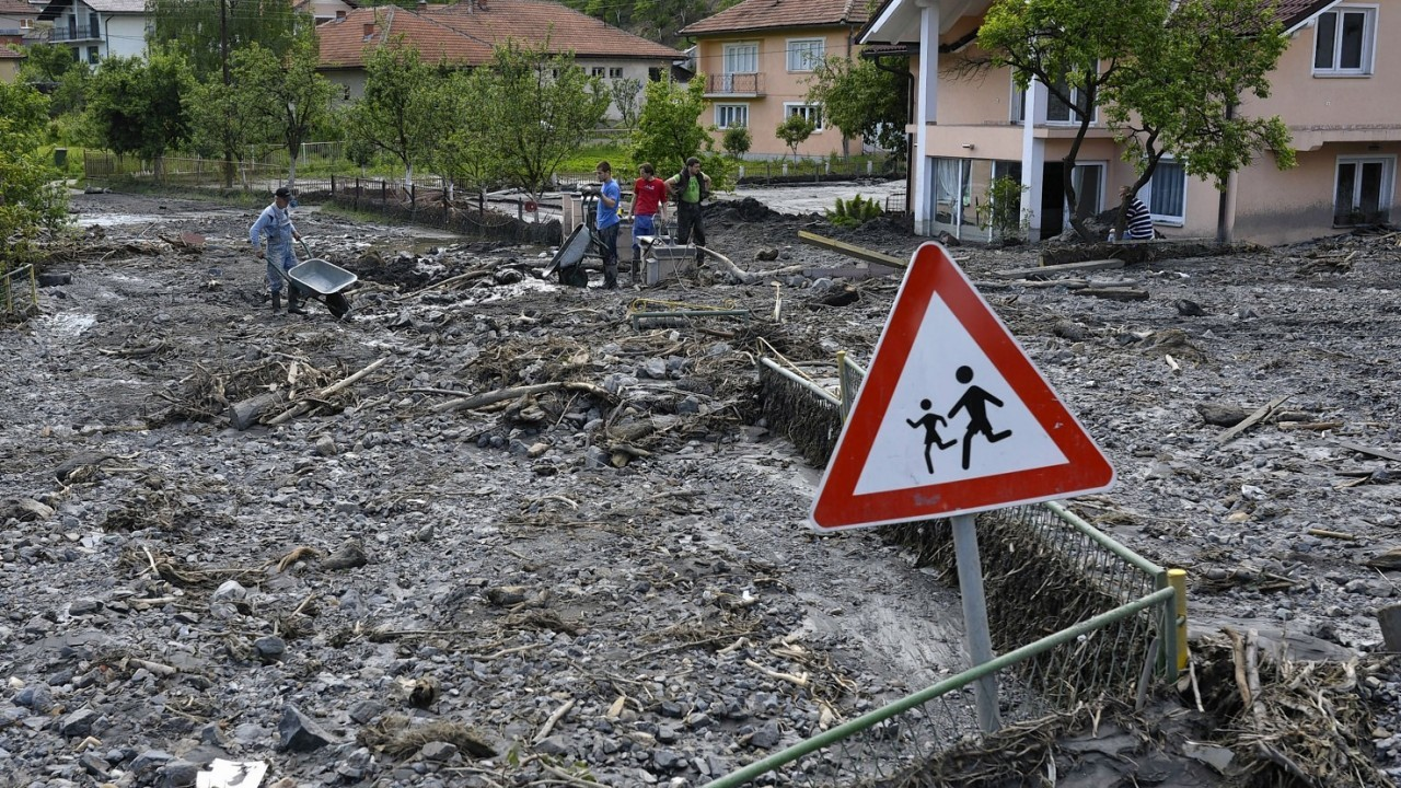 Residents clean streets of mud and rubble after a landslide at the village of Topcic Polje, near the Bosnian town of Zenica, 90 kilometers north of Sarajevo