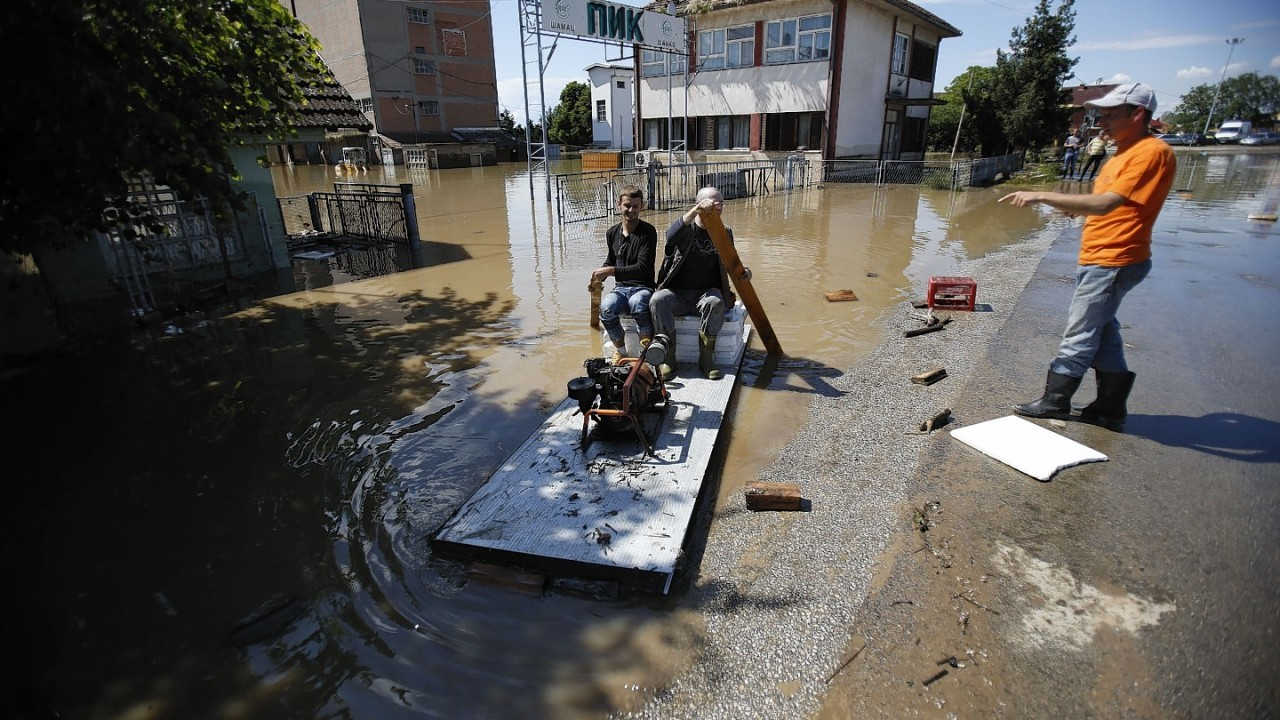 Bosnian people on a improvised raft  transport an electric generator to a house in floodwater near the Bosnian town of Bosanski Samac along river Sava