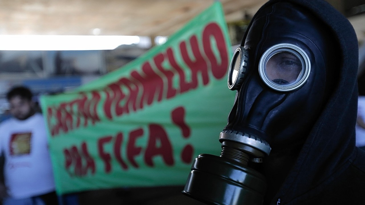 """A man with a gas mask stands next to a banner that reads in Portuguese, """"Red Card for FIFA"""",  during a protest against the money spent on the World Cup, in Brasilia, Brazil,"""