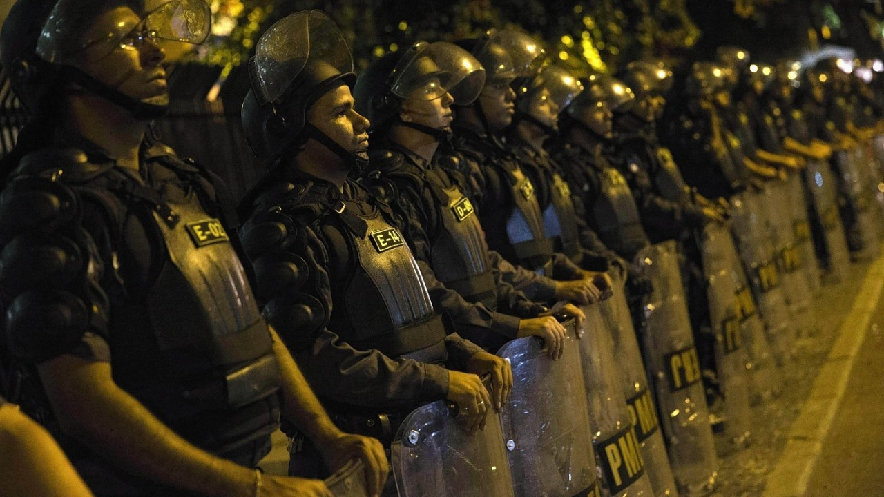 Police officers stand guard during a protest against the money spent on the World Cup preparations, in Rio de Janeiro, Brazil,