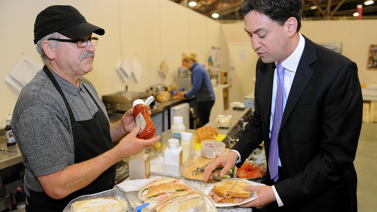 Labour leader Ed Miliband buys a bacon sandwich from cafe owner Antonios Foufas at New Covent Garden Market in London as he kicks off a day of campaigning on the eve of the local and European elections