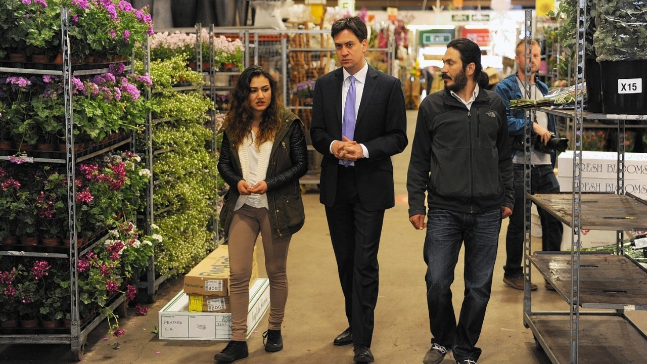 Labour leader Ed Miliband talks with a couple of traders at New Covent Garden Market in London as he kicks off a day of campaigning on the eve of the local and European elections
