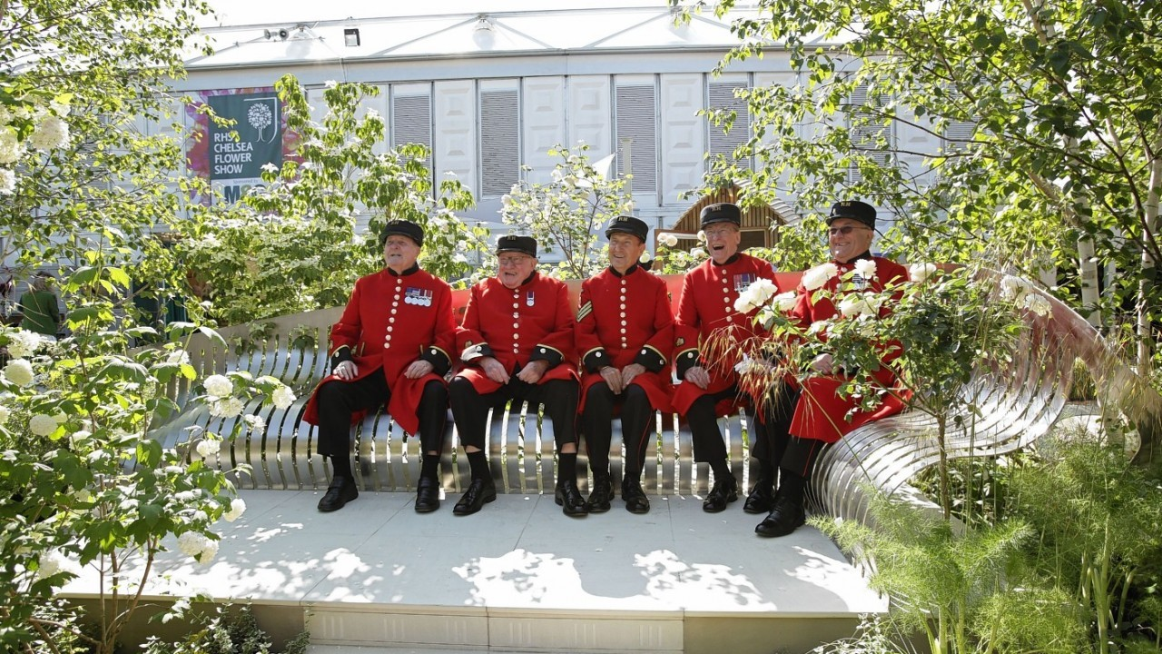 Five Chelsea Pensioners enjoy a quiet moment on a bench in a London garden square, designed by gold medal winner Jo Thompson