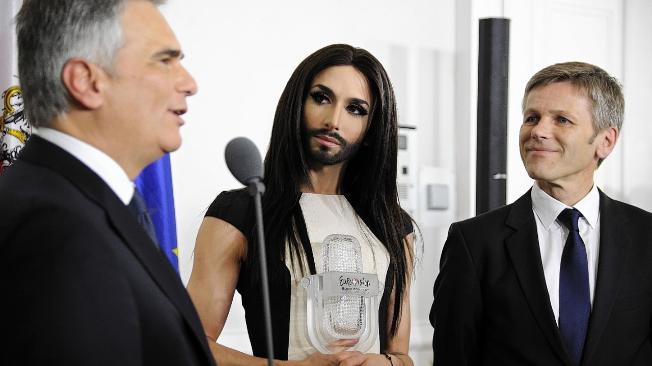 Austrian Federal Chancellor Werner Faymann, left, and Federal Minister for Arts and Culture Josef Ostermayer, right, welcome Austrian singer and Eurovision Song Contest winner Conchita Wurst at the federal chancellery in Vienna