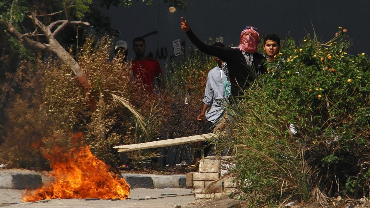 A protester throws a stone at security forces during clashes in a student housing area of Al-Azhar University in Cairo, Egypt