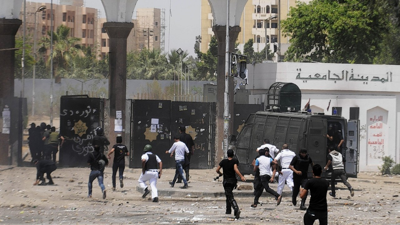Egyptian security forces run into a student housing area of Al-Azhar University during clashes with student protesters in Cairo, Egypt,