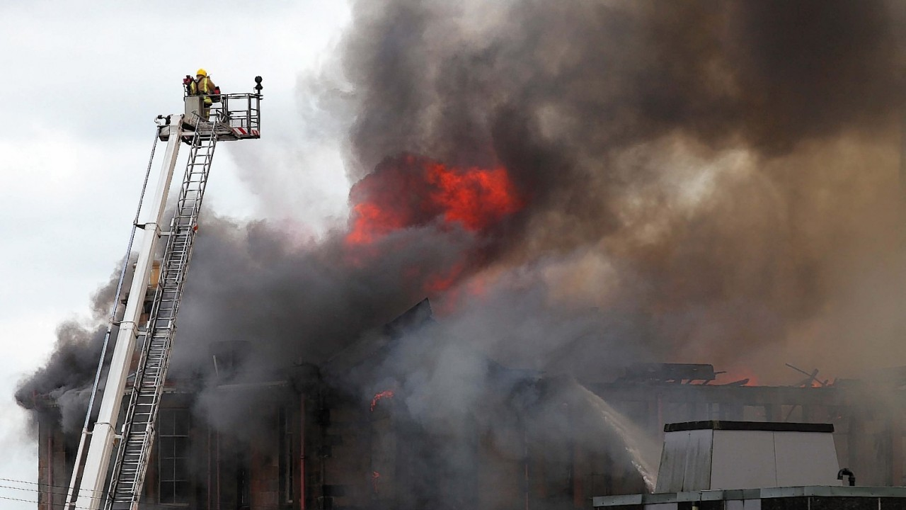 Fire fighters at the scene of a fire at a former school on Broomloan Road in Govan, Glasgow