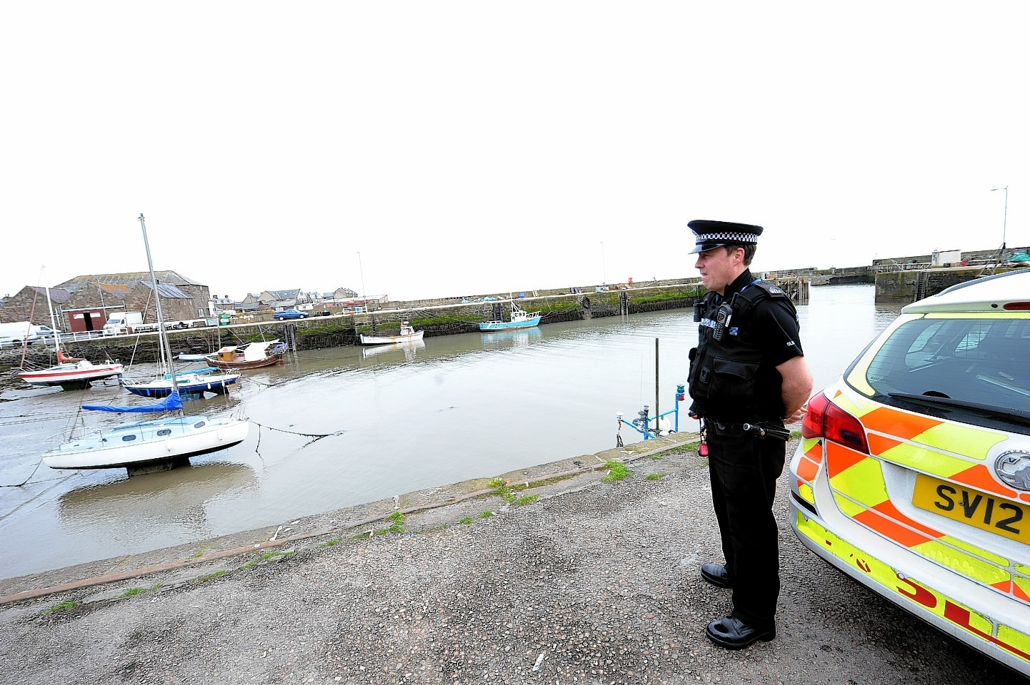 A police officer at Gourdon Harbour on May 20, when the fishermen went missing