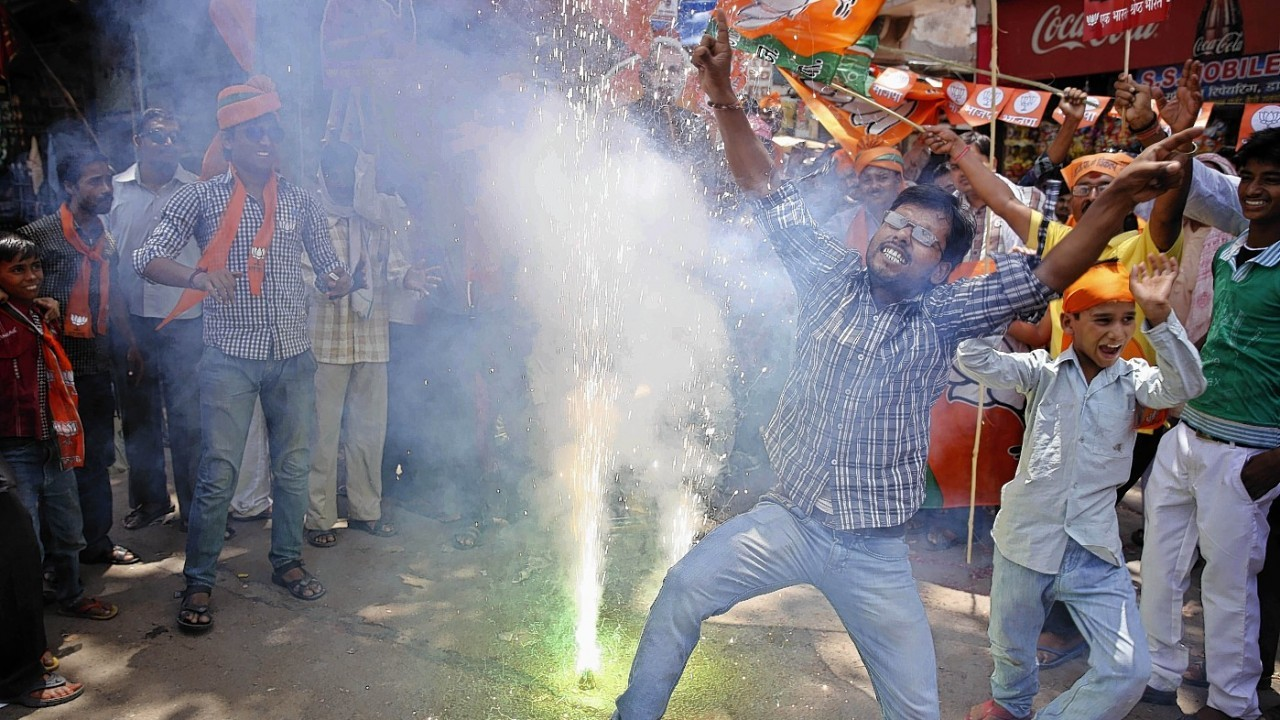 Bharatiya Janata Party (BJP) supporters dance and burst firecrackers to celebrate the news of early election result trends in Allahabad, in the northern Indian state of Uttar Pradesh