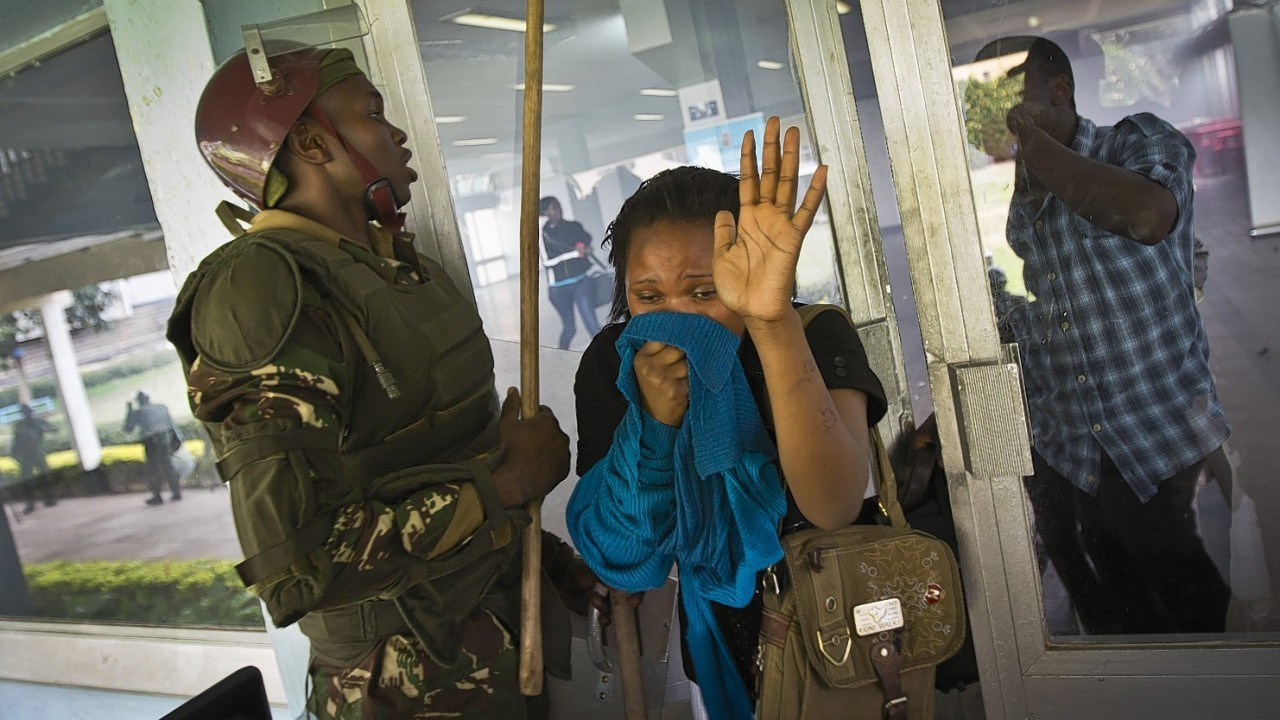 A student or member of university staff overcome by tear gas holds a cloth to her face and puts her hands in the air as she tries to escape from a tear-gas-filled building inside Nairobi University's main campus in downtown Nairobi, Kenya