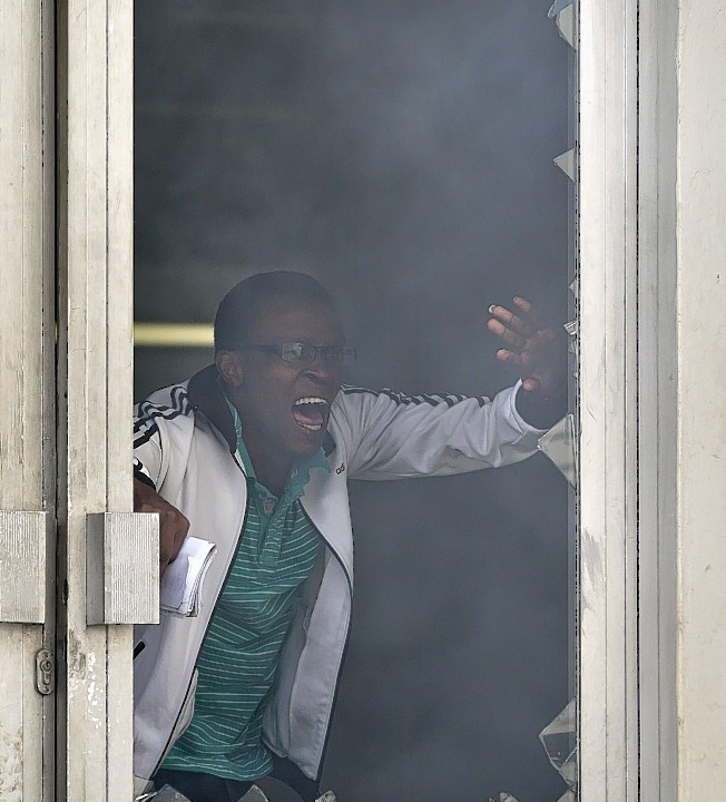 A student or member of university staff tries to escape from a tear-gas-filled building, before being chased back inside by riot police, inside Nairobi University's main campus in downtown Nairobi,