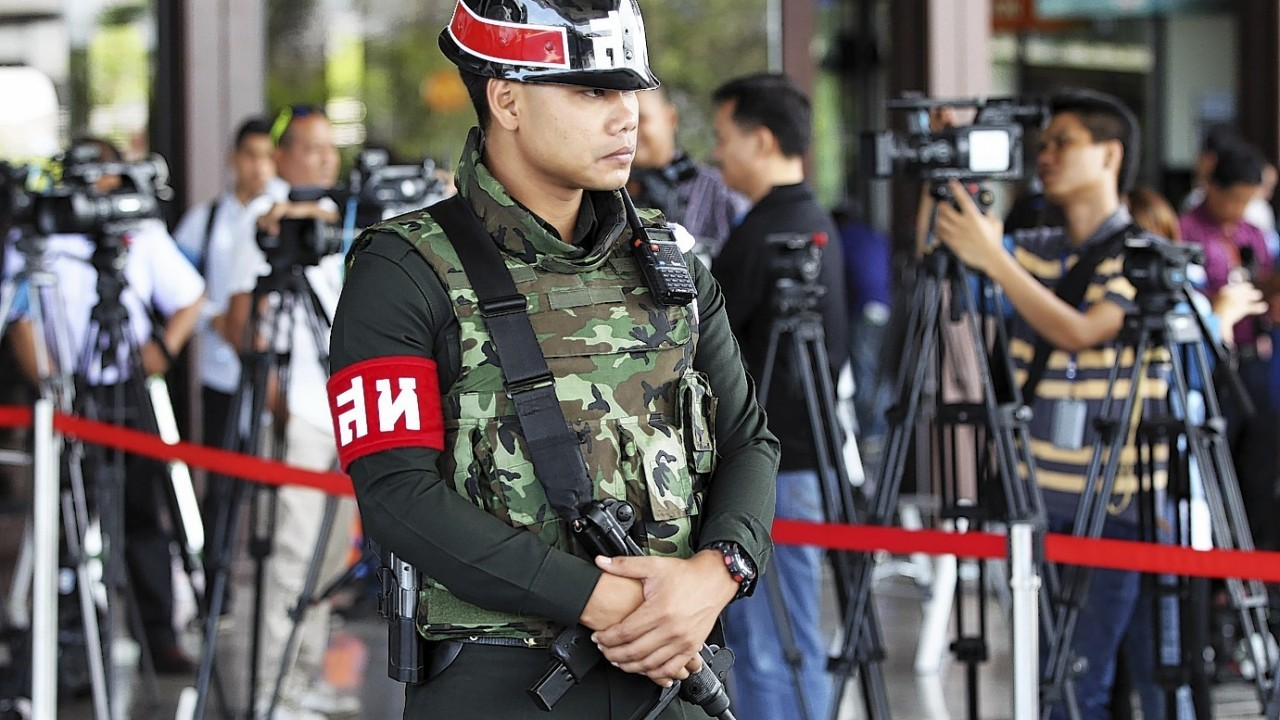 An armed Thai military police stands guard at the entrance to a hall of the army club prior to a meeting between Thai Armed Forces Chiefs and high ranking officials Tuesday, May 20, 2014 in Bangkok