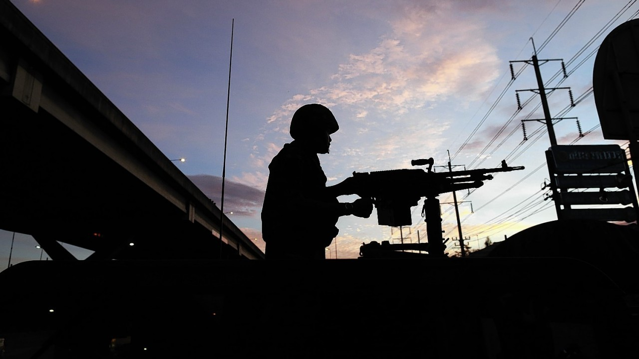 A Thai soldier mans his machine gun atop a military vehicle outside the Centre for the Administration of Peace and Order (CAPO) after soldiers were sent in to seized the center Tuesday, May 20, 2014 in Bangkok