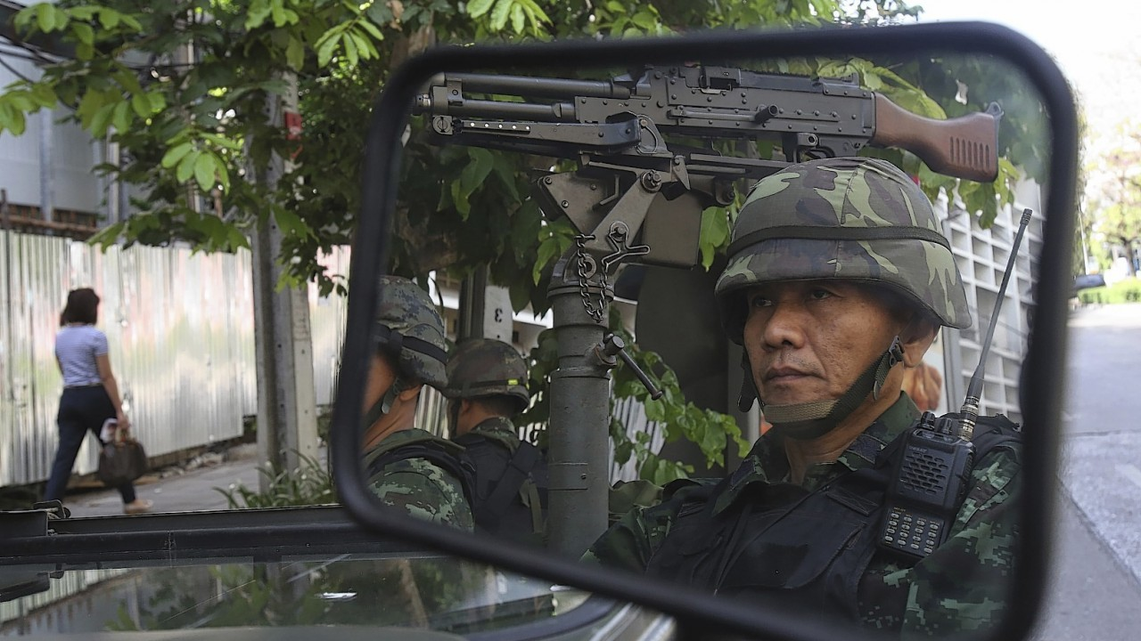 Thai soldiers are reflected in a mirror while guarding the Thai police headquarters Tuesday, May 20, 2014, in Bangkok
