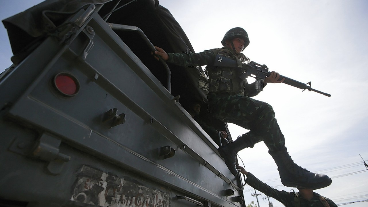 A Thai soldier jumps off a military truck after arriving at a pro-government rally site on the outskirts of Bangkok, Thailand