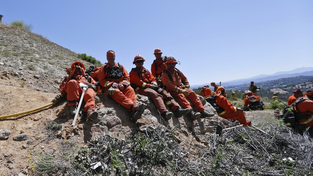 Firefighters take a break on a hillside after hours of work Thursday, May 15, 2014, in San Marcos, Calif.