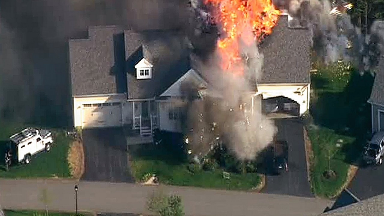 Local US TV images after a New Hampshire police officer was shot to death after he responded to a domestic disturbance at a home that later exploded and burned