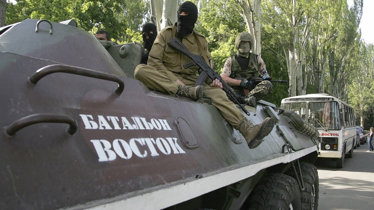 "Pro-Russian gunmen atop of an armored personnel carrier with the words read ""Battalion Vostok (East) "" patrol a street in Donetsk, Ukraine"