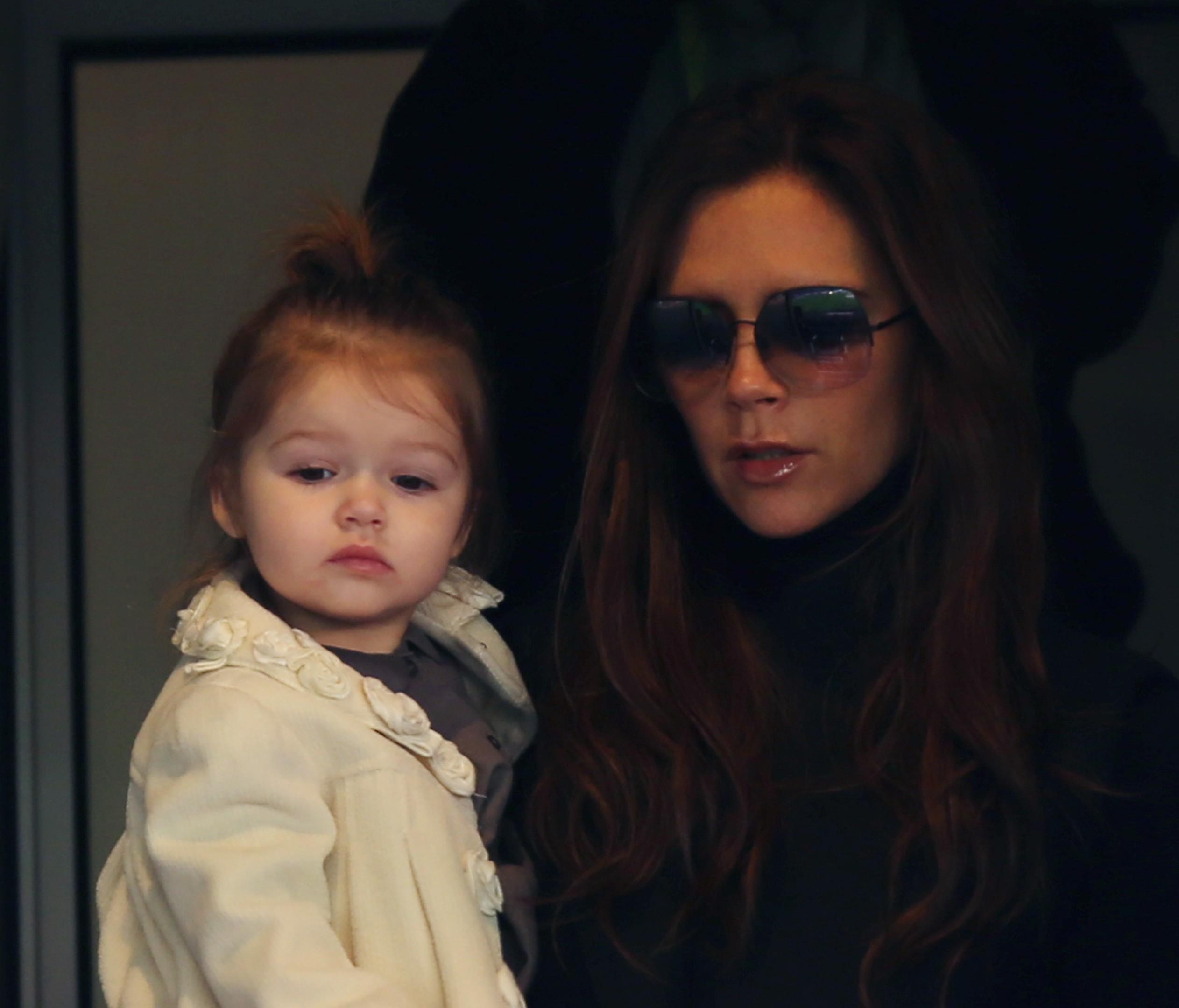 Victoria Beckham holding her daughter Harper