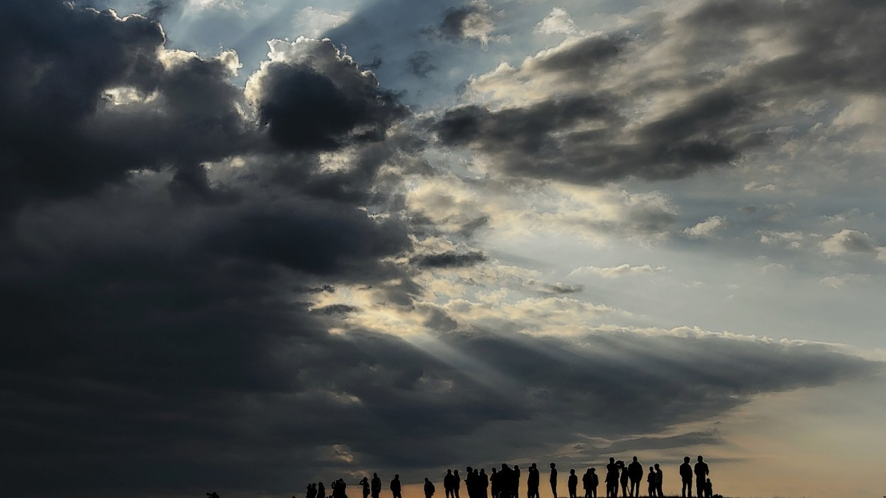 Spectators watch under heavy clouds the a landing of  solar-powered Solar Impulse 2 aircraft  after its first flight