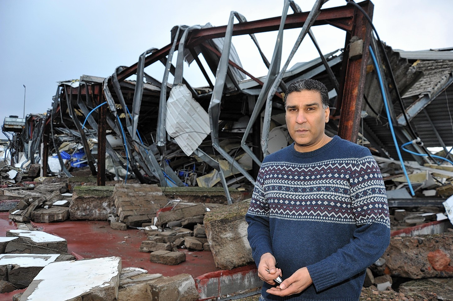 Nasar Rashid in front of his ruined factory