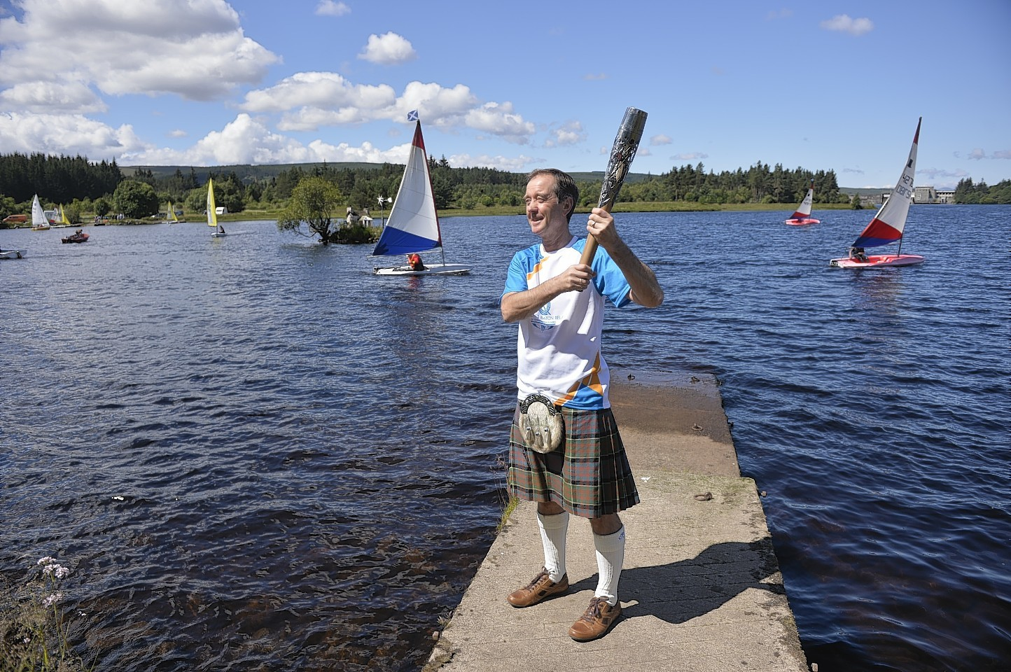 Thomas Mathieson carrying the Glasgow 2014 Queen's Baton through Lairg in the Scottish Highlands.