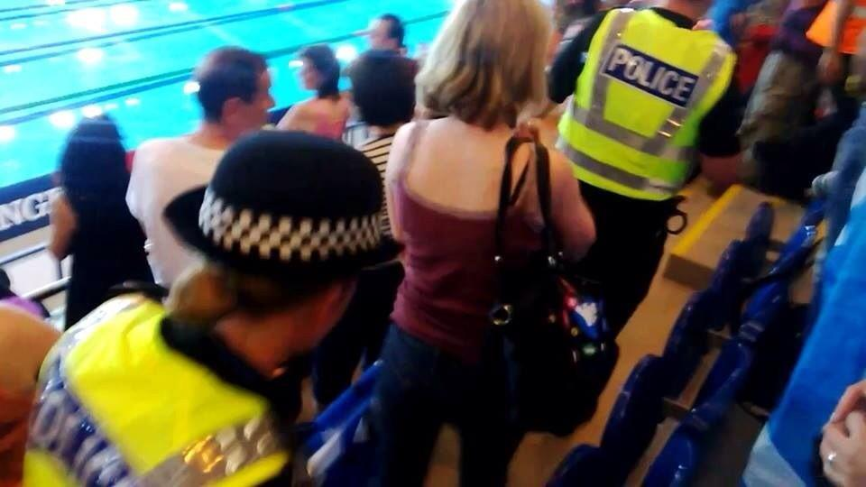 The woman is escorted from the arena by police