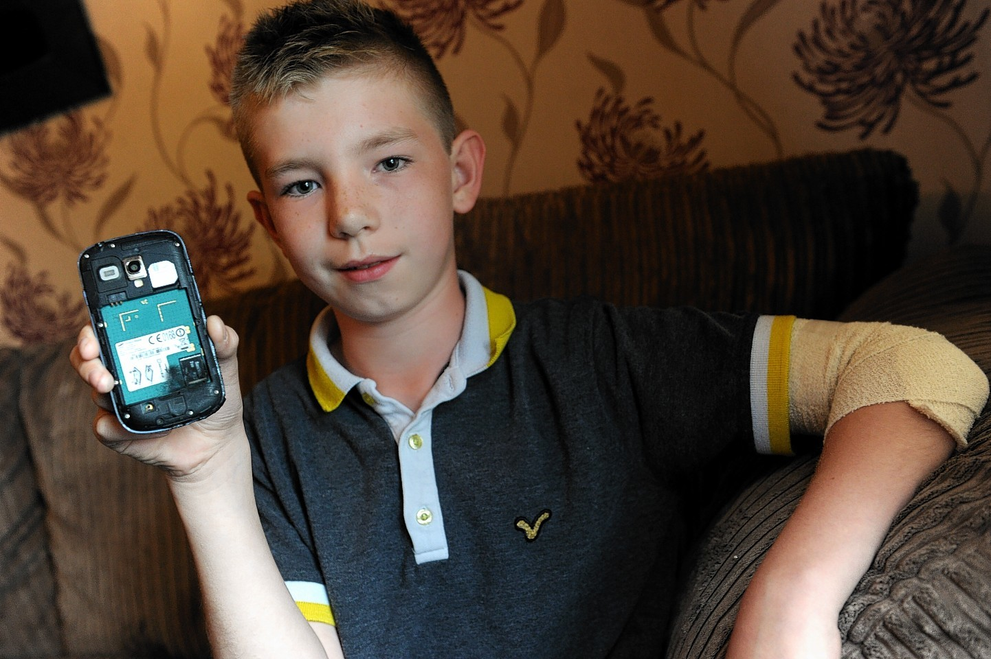 Tyler Harrison shows the phone which was charging when the flames started