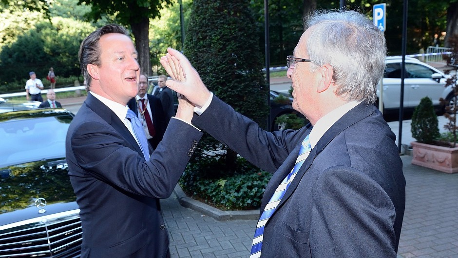 "Jean-Claude Juncker ""high-fiving"" Prime Minister David Cameron at the European Parliament in Brussels, Belgium."