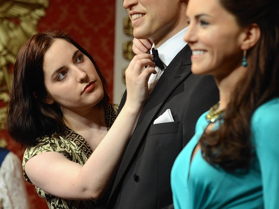 Wardrobe assistant Luisa Compobassi applies finishing touches to the wax figures of the Duke and Duchess of Cambridge as they are unveiled at Madame Tussauds, London.