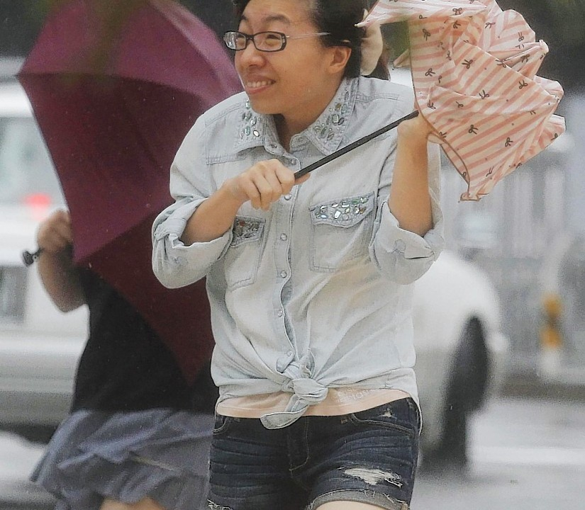 Women walk amid strong winds on a street in Naha, Okinawa, southern Japan, Tuesday, July 8, 2014