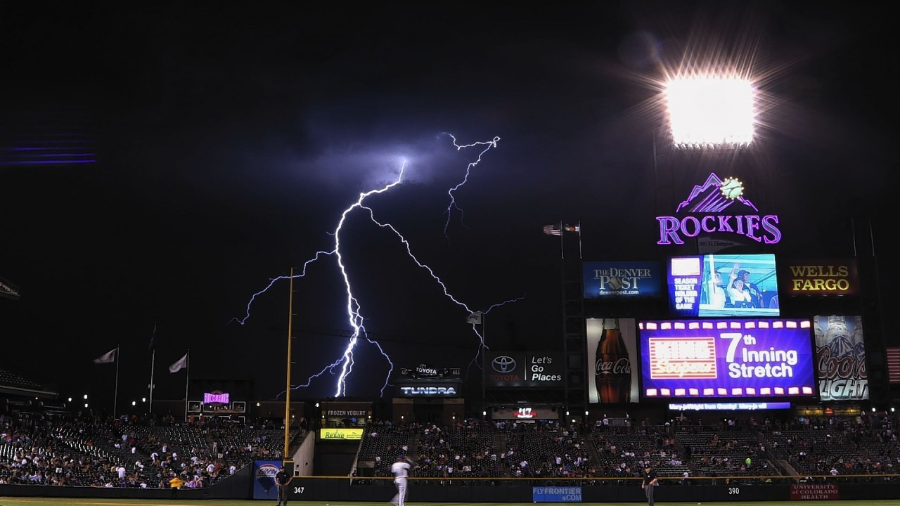 Lightning strikes in the background during the seventh inning of an MLB baseball game between the Colorado Rockies and the San Diego Padres on Monday, July 7, 2014, in Denver.