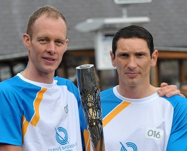 David Smith (left) carrying the baton with shinty star Ronald Ross in Aviemore