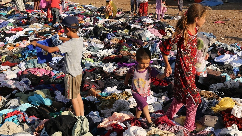 Displaced Iraqis from the Yazidi community look for clothes to wear among items provided by a charity at the Nowruz camp in Derike, Syria (AP)