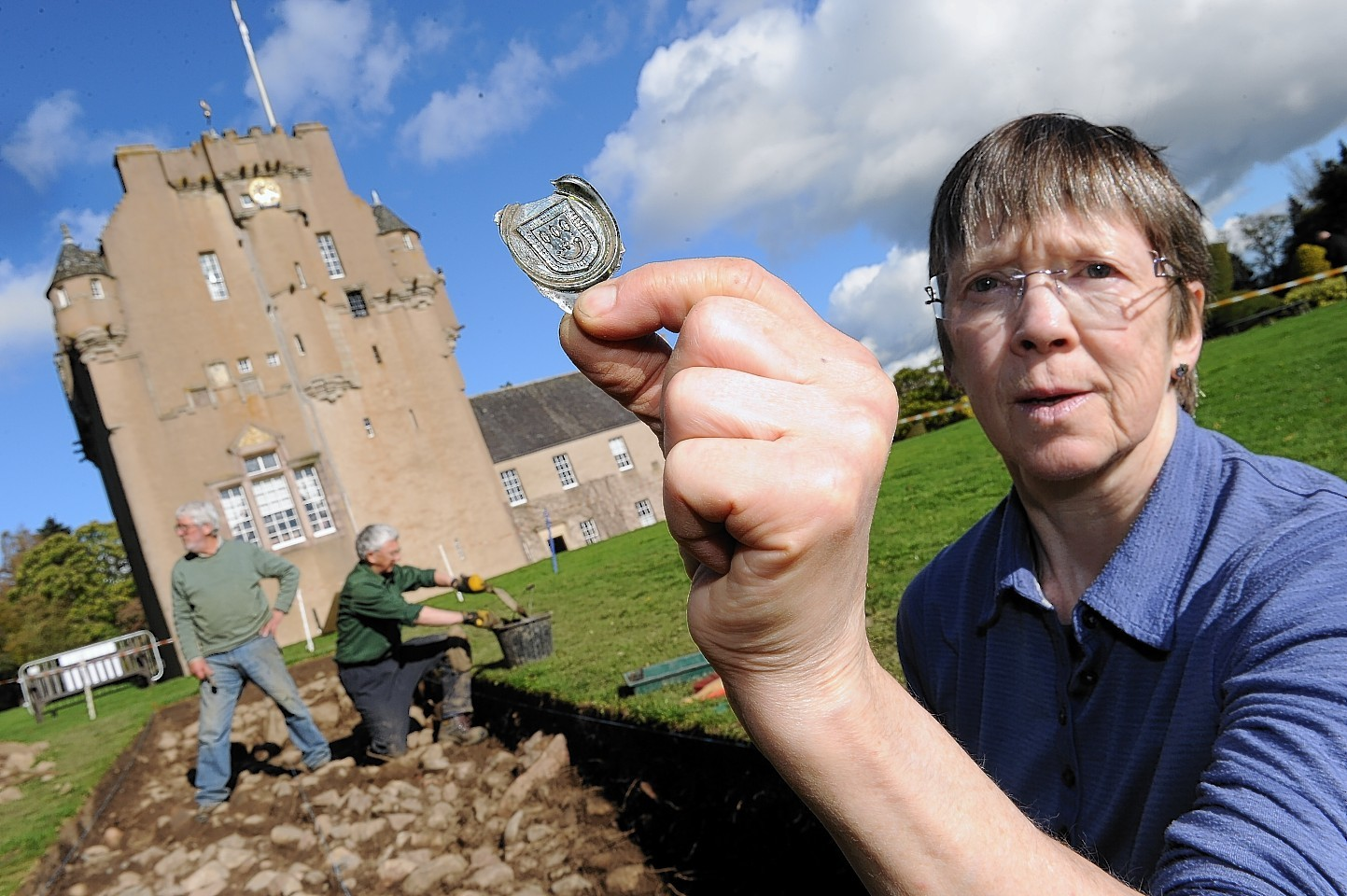 Volunteer Veronica Ross with a bottle seal showing the Burnett Coat Of Arms found at an archaeological dig at Crathes Castle.