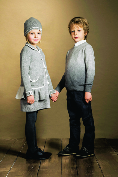 Girl wearing grey coat with front pockets, diagonal knot stitch set and hat. Boy wearing Corean shirt with contrast boarders and jumper, all from Cashmirino