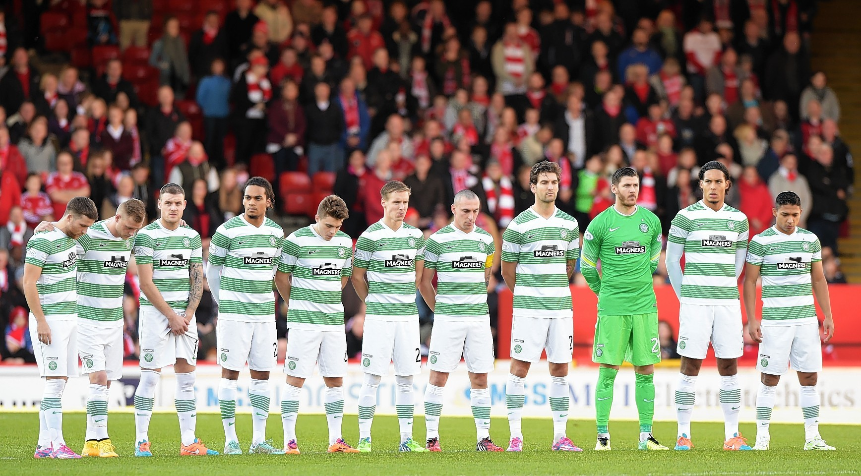 The Celtic players pay their respects prior to the match at Pittodrie.