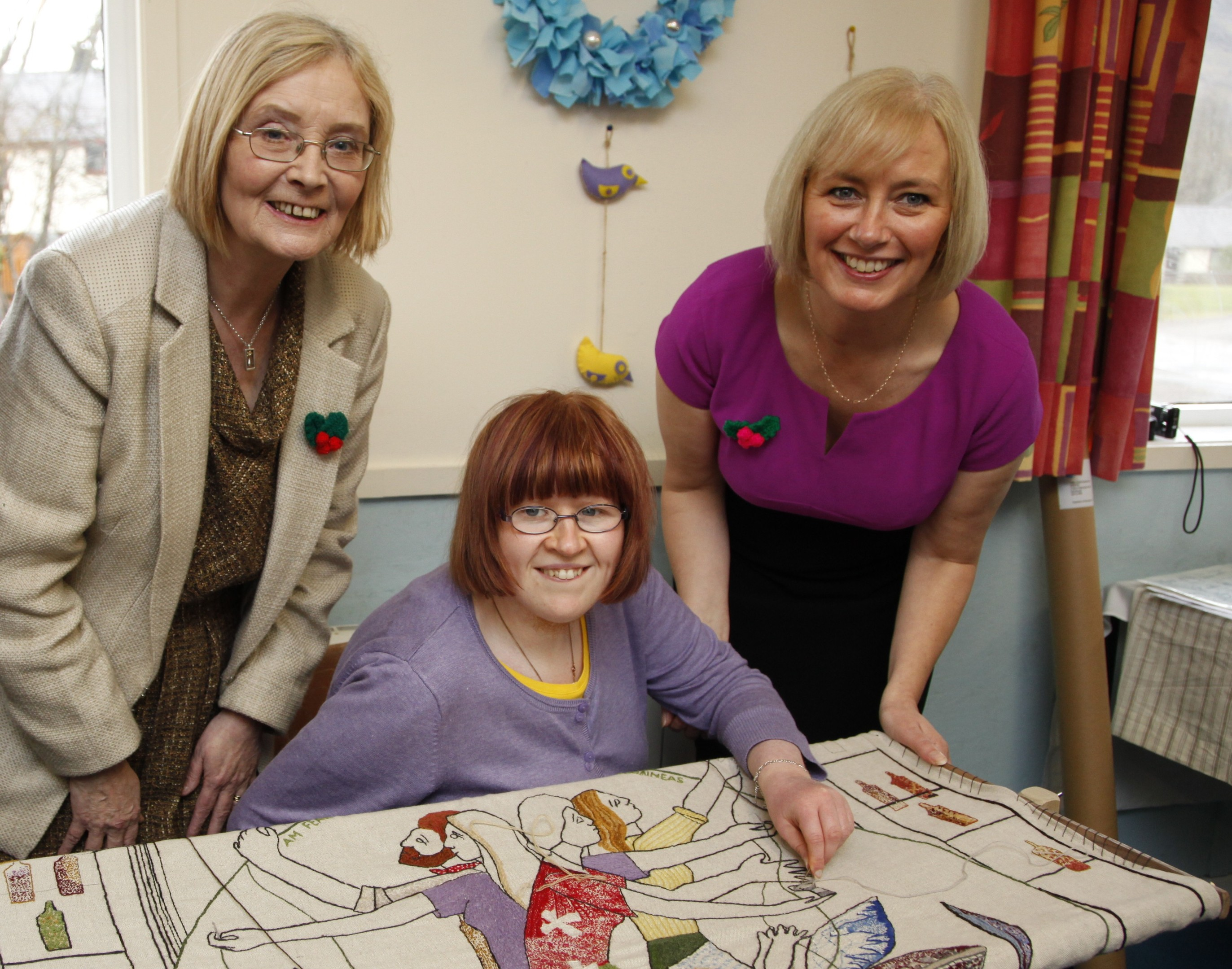 Presiding Officer Tricia Marwick MSP and Lyn Johnson, of Nimble Fingers, watch Donna MacKay adding a couple of stitches to the tapestry