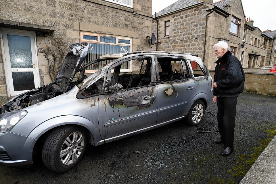 Robbie McNab inspects the damage after the car fire