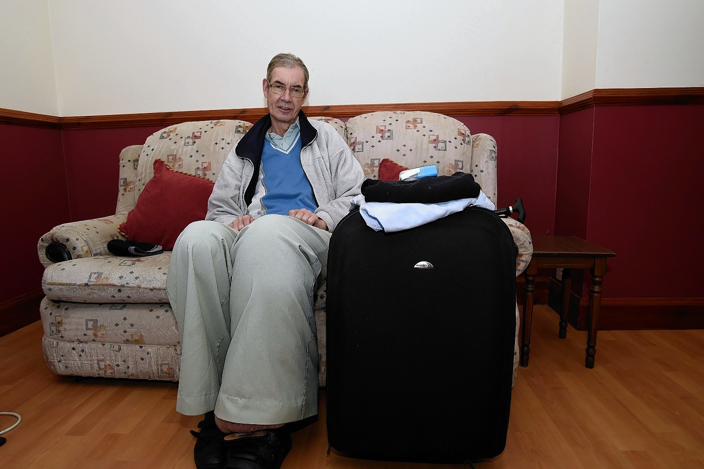 Michael Cull sits by a suitcase he had packed ready for surgery