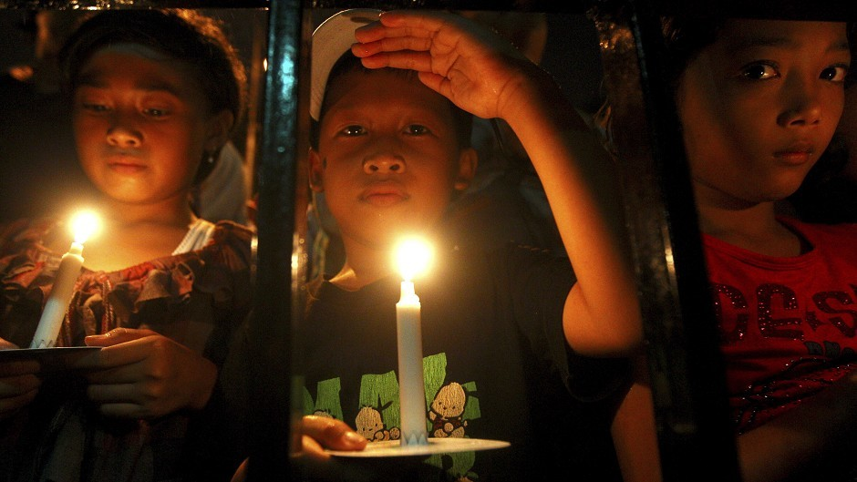 Indonesian children hold candles to pray for the victims of AirAsia Flight 8501 in Surabaya (AP)