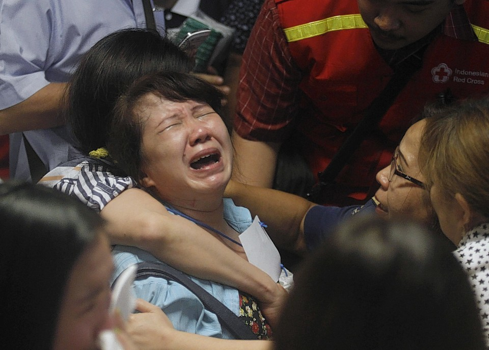 Relatives of passengers of the missing AirAsia flight QZ 8501 react to the news