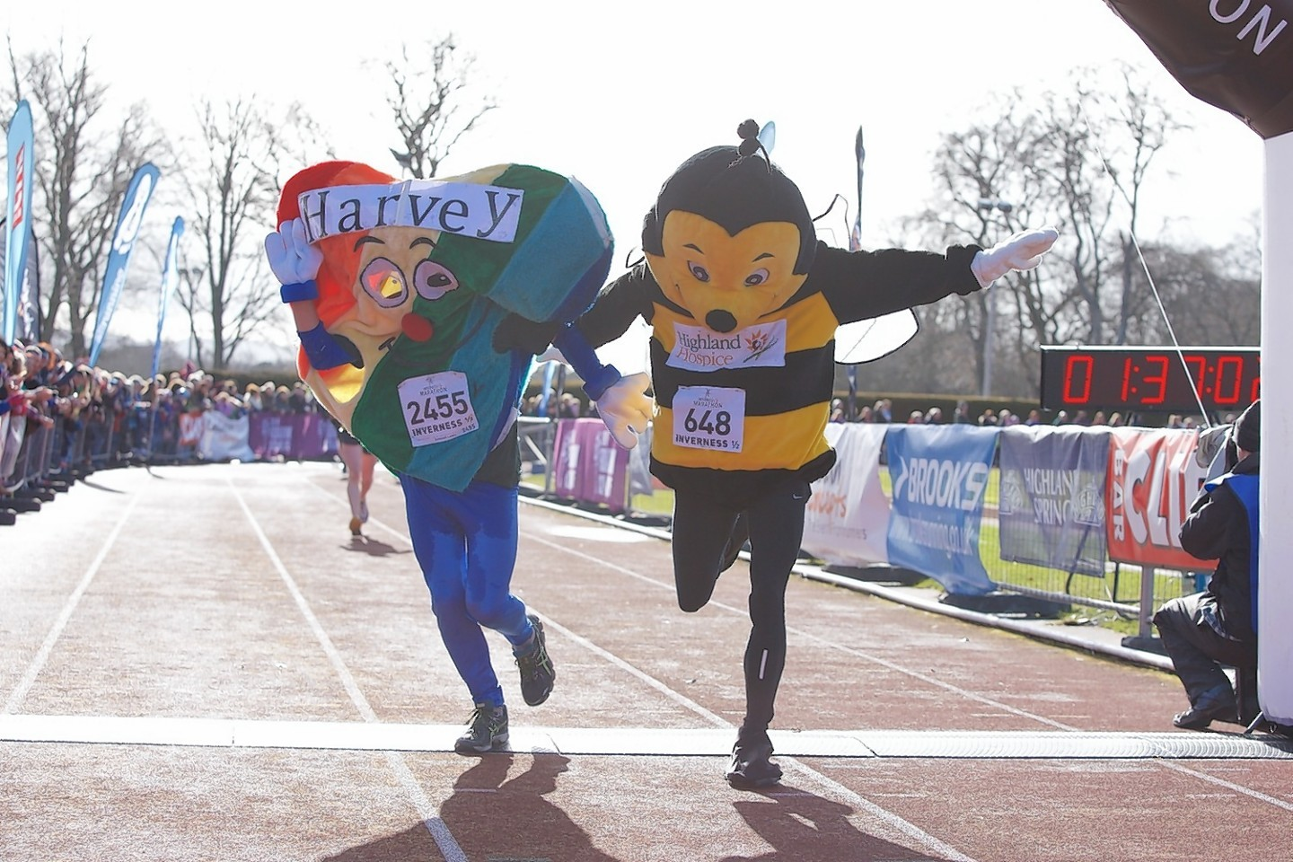 Harvet the Heart and Bobby the Bee cross the finishing line