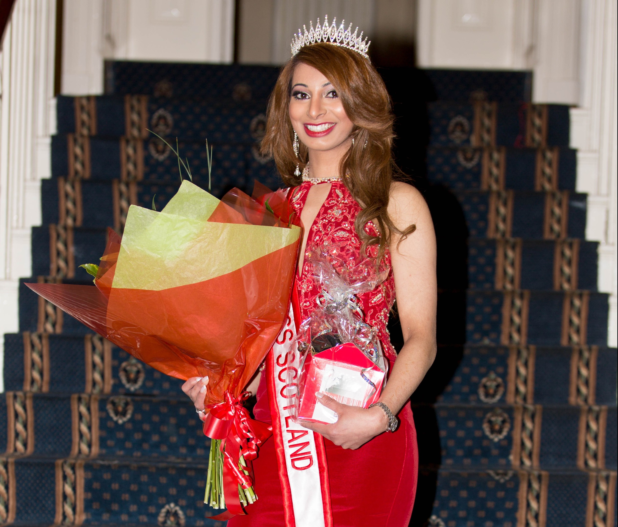 Madiha Iqbal posing triumphantly after becoming Miss Progress Scotland