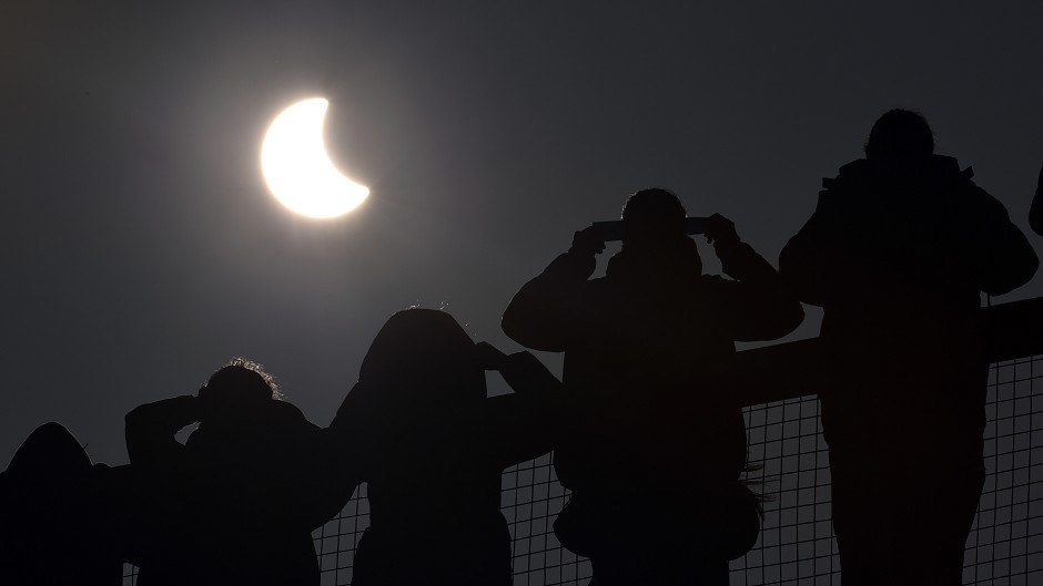 People watch as an eclipse of the sun begins over the Eden Project in Cornwall