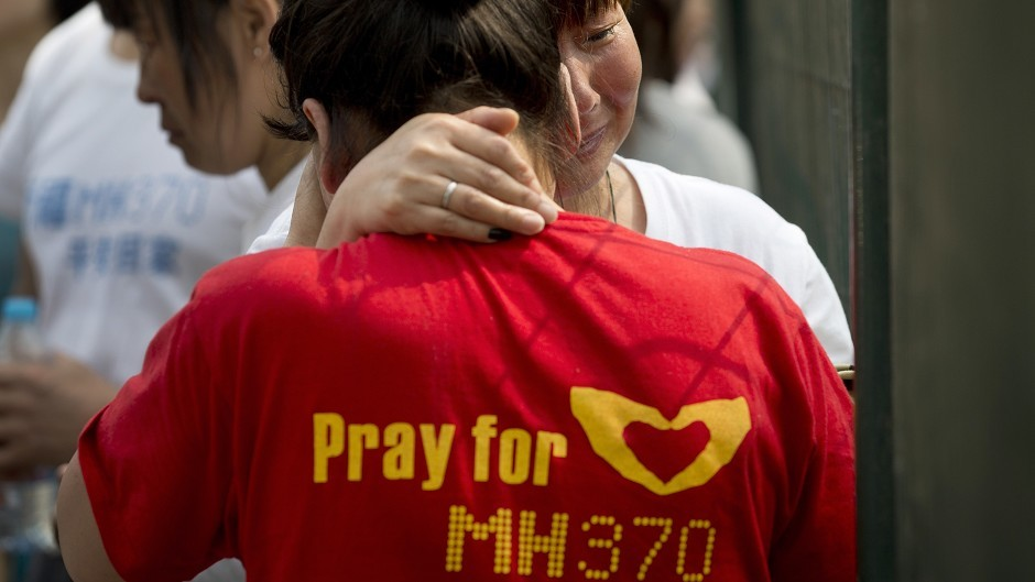 Chinese relatives of passengers on board the missing Malaysia Airlines MH370 plane cry during a protest at the Malaysian embassy in Beijing (AP)