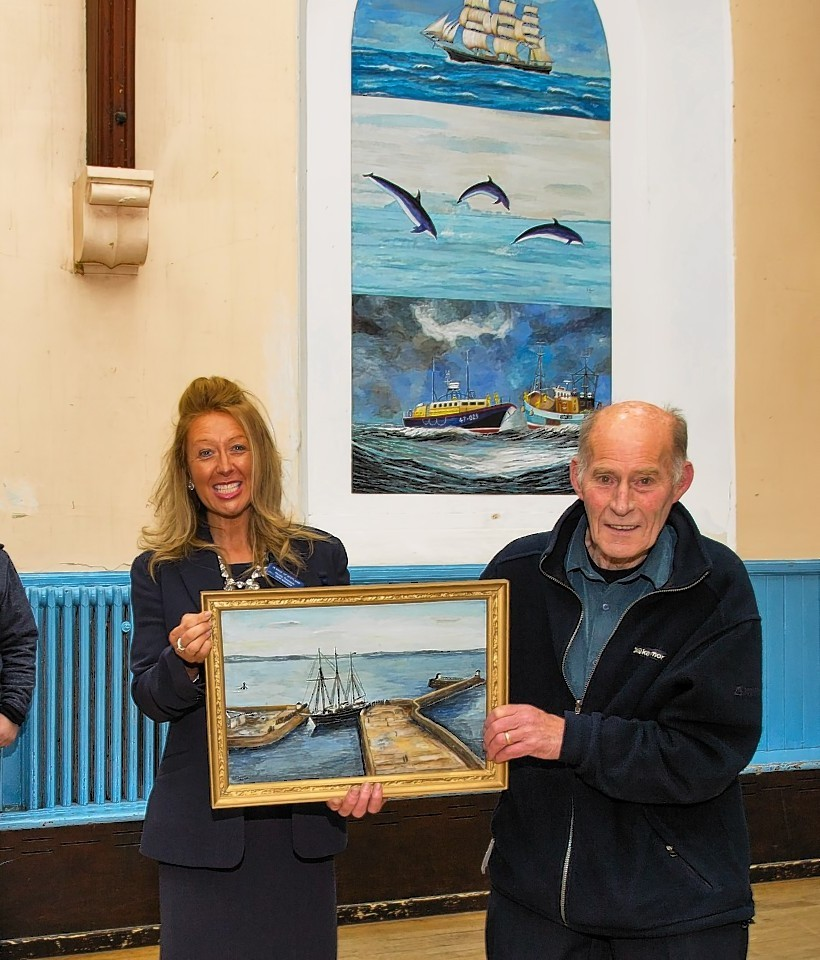 Nicola Thomson presents the painting to Neil Smith, chairman of the Community Hall.