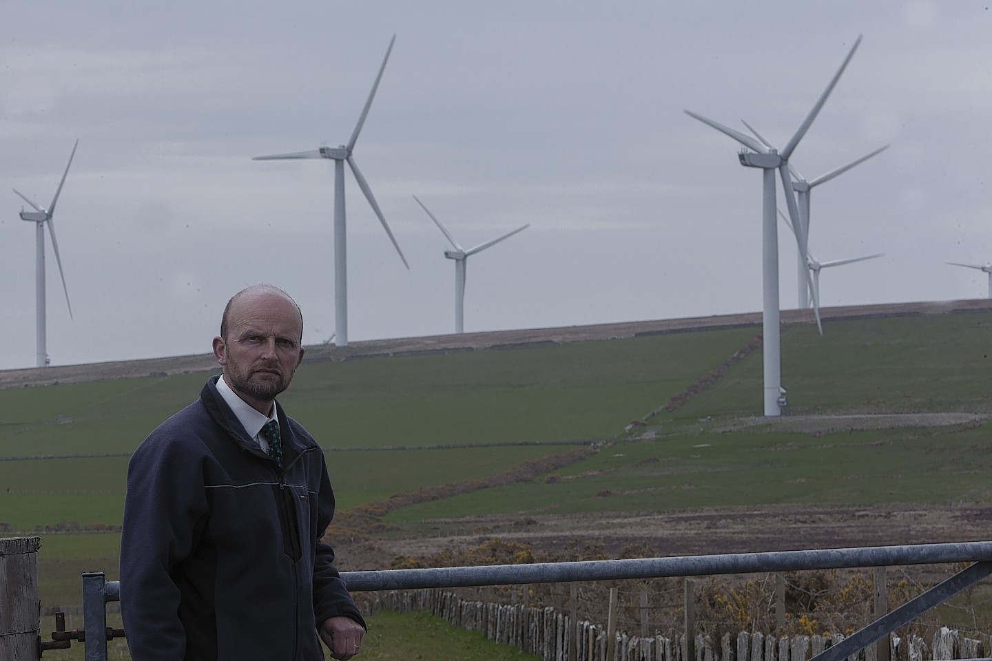Caithness rural councillor Matthew Reiss with one of the many windfarms in the background.