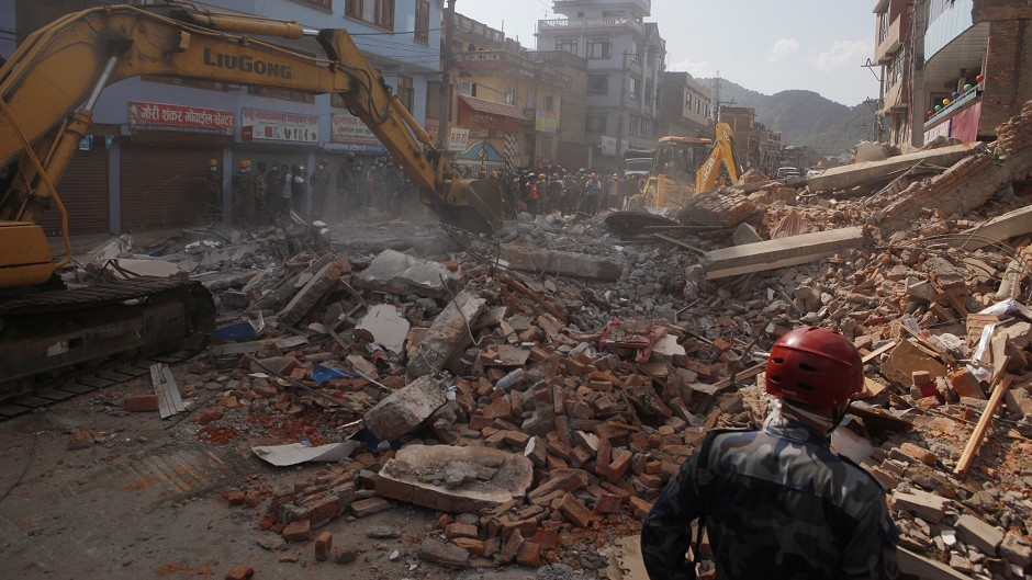 Earthmovers clear the debris after a building collapsed in Kathmandu, Nepal. (AP)